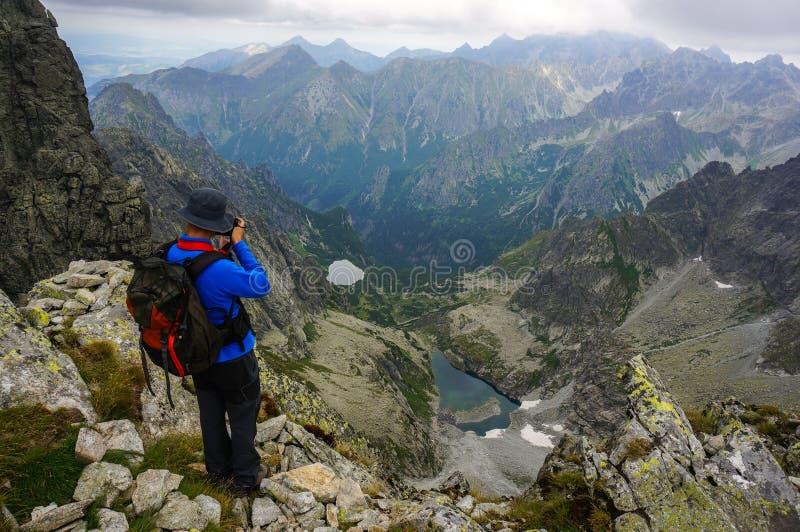 Photographe prenant une photo dans les montagnes photos stock