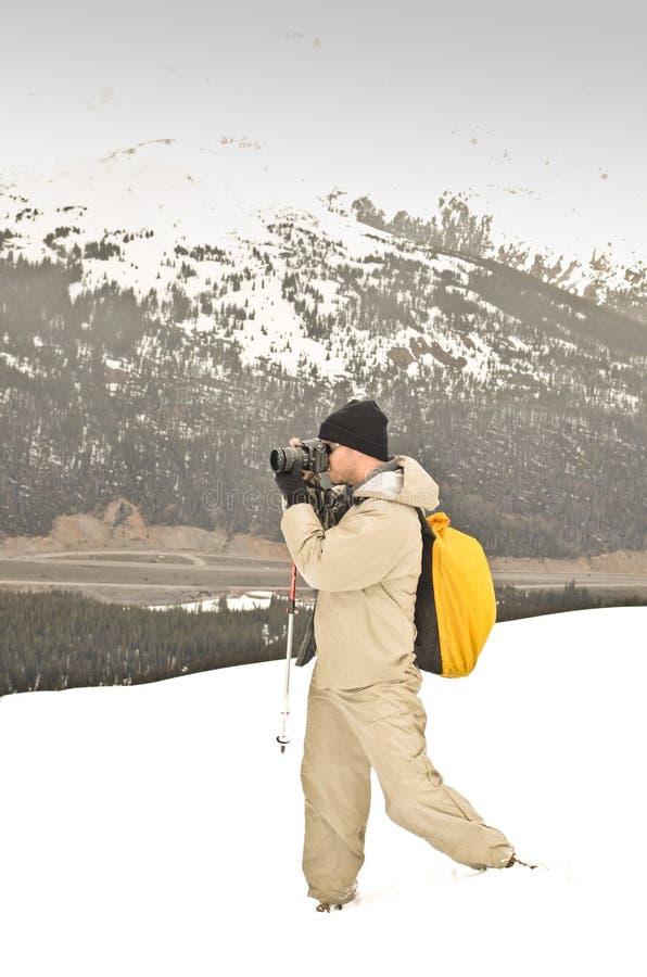Photographe prenant une photo sur une montagne neigeuse photographie stock