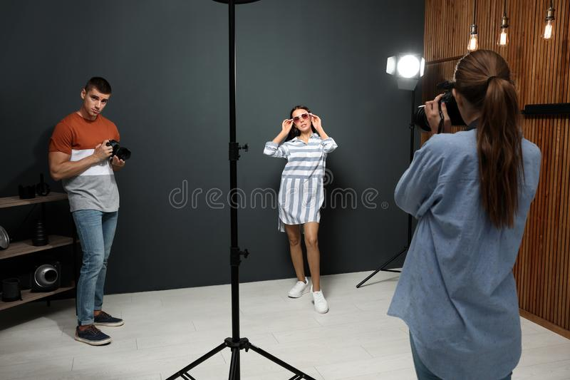 Photographe professionnel avec l'assistant prenant la photo du jeune homme photographie stock