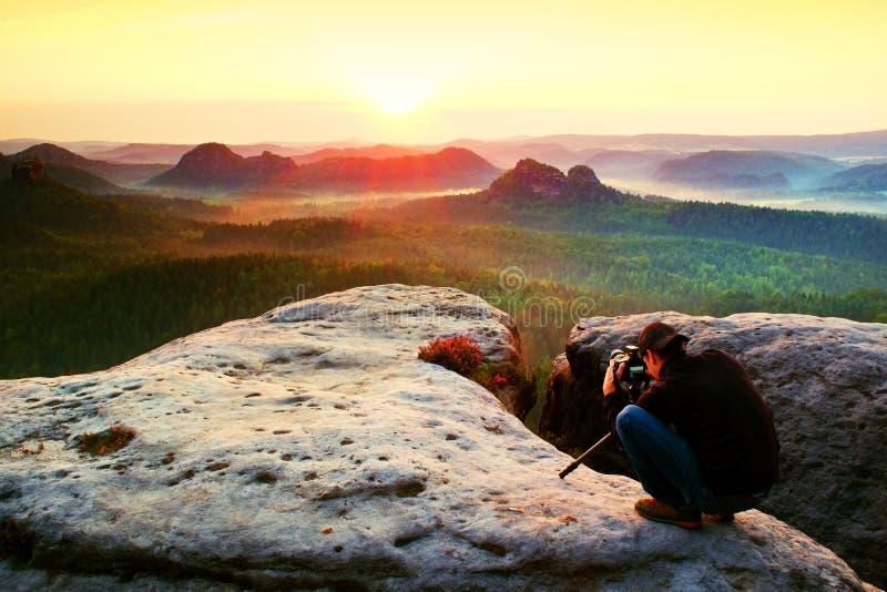 Photographe professionnel avec le trépied sur la falaise et la pensée Paysage rêveur de vieille galoche, lever de soleil brumeux  photos libres de droits