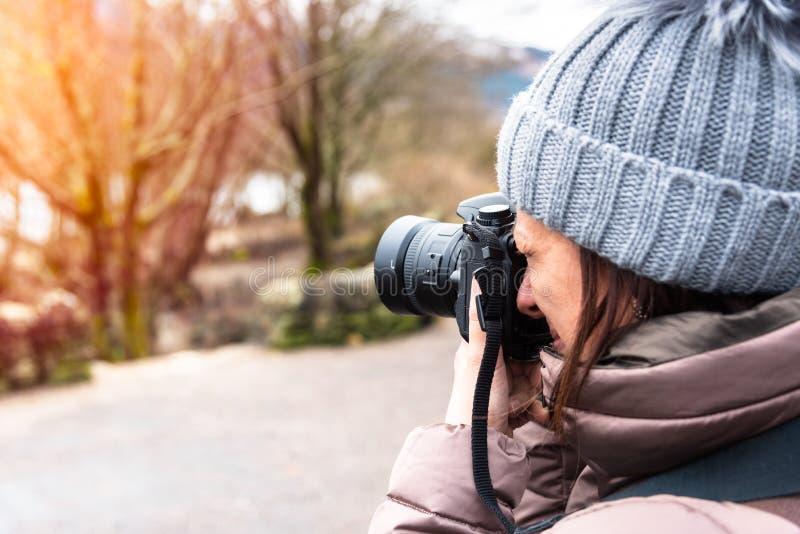 Photographe professionnel de femme prenant des photos extérieures en hiver image libre de droits