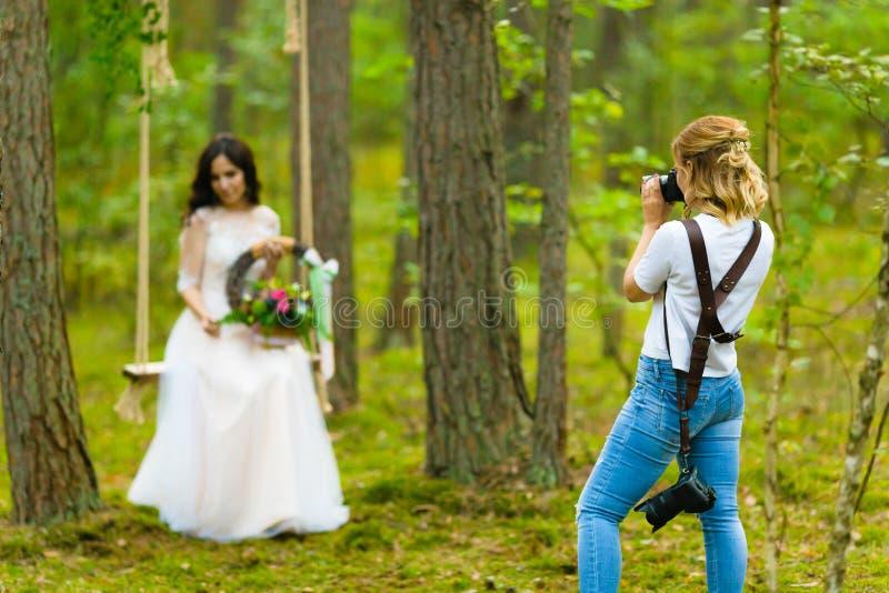 Photographe professionnel de mariage prenant les portraits en gros plan de la jeune mariée photos stock