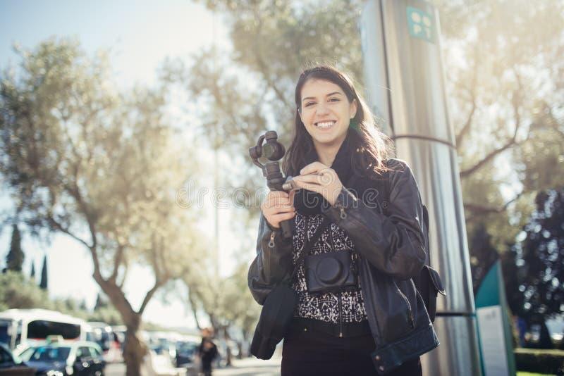 Photographe professionnel féminin de voyage de videographer faisant la vidéo dans la cuvette de la résolution 4K des rues photos libres de droits