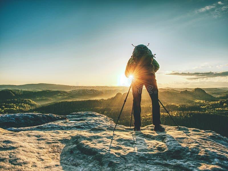 Photographe sur la montagne au-dessus de la vall?e avec la brume de matin photos libres de droits