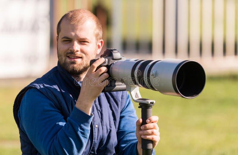 Photographe tenant l'appareil-photo photographie stock