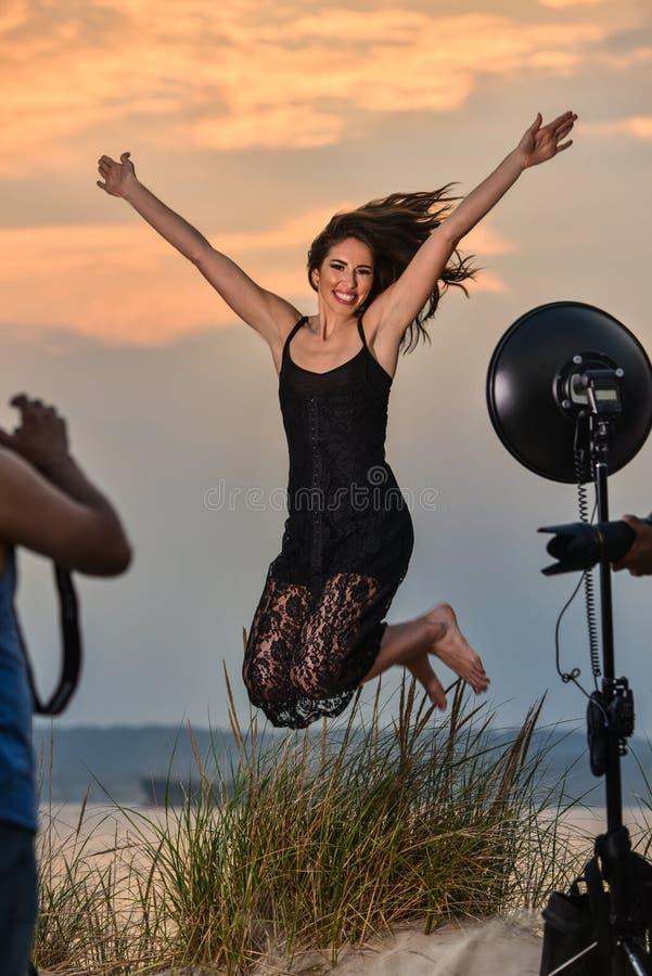 Photographe tirant le modèle sautant de belle brune à la plage photo stock