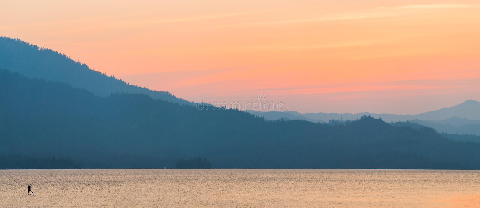Brilliant, colorful sunset over Whiskeytown Lake in Northern California with a paddleboarder in the water royalty free stock images