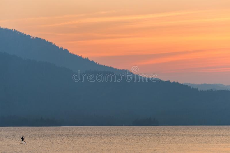 Brilliant, colorful sunset over Whiskeytown Lake in Northern California with a paddleboarder in the water royalty free stock photos