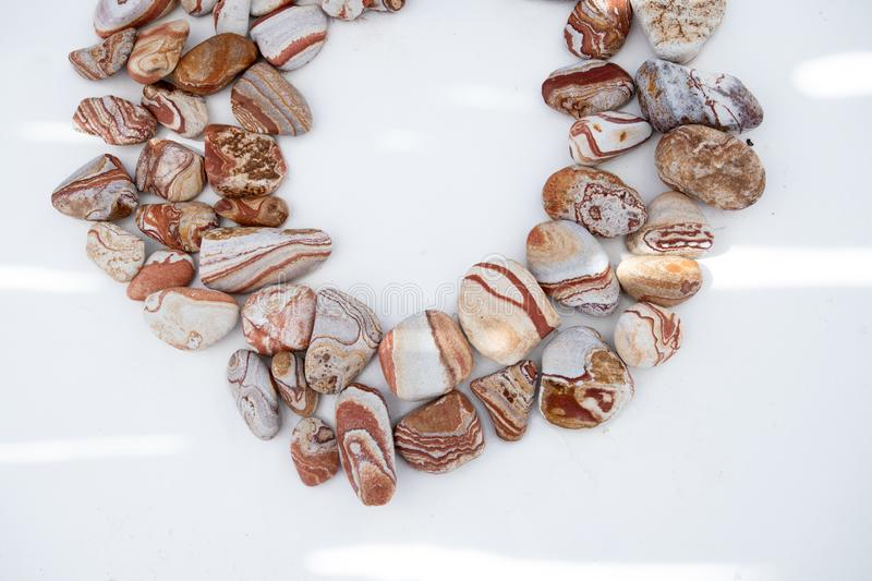 Circle Of Southwestern River Sand Stones. Photographed in splashes of light on white background red sandstone river rocks grouped in a circle stock image