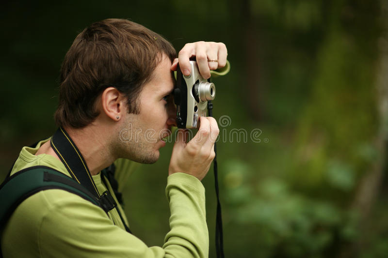 Photographer. Shooting with compact camera in forest stock images