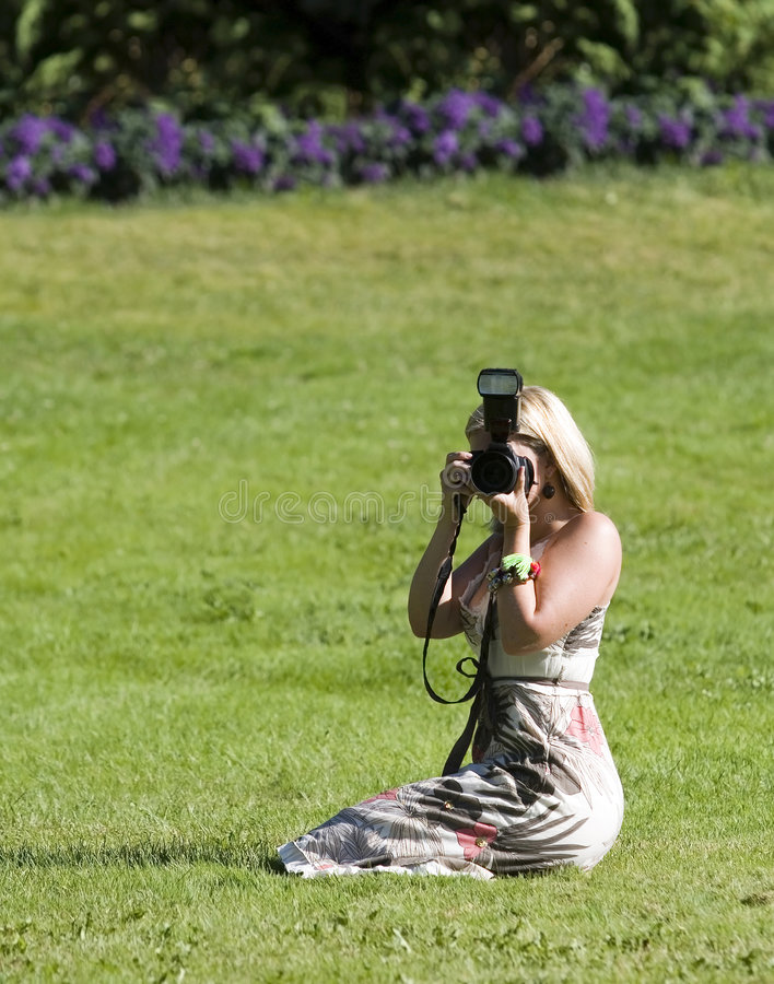 Photographer. Woman outdoors taking a picture stock image