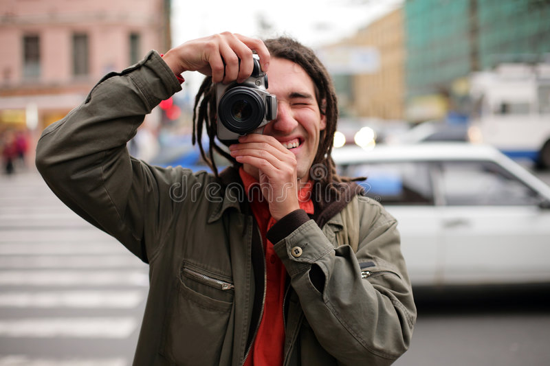 Photographer. Young photographer taking a photo with DSLR camera stock photos