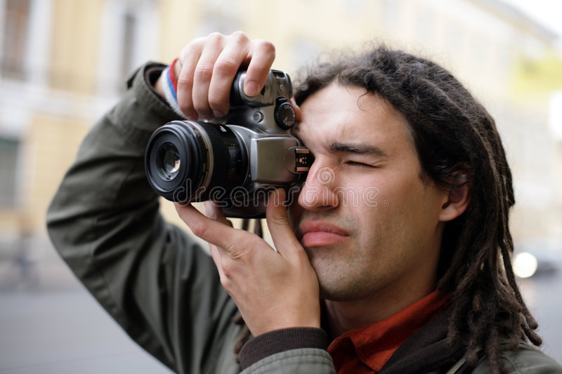 Photographer. Taking a photo with DSLR camera stock image