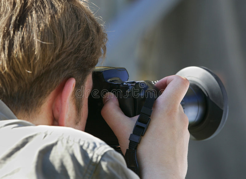 Photographer. The photographer with a camera works stock photography