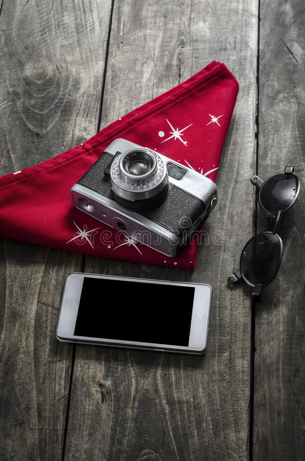 Photographer accessories on table. Photographer accessories, camera, phone and glasses on wooden surface stock photography