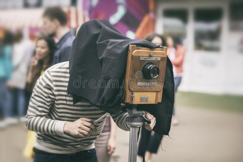 Photographer with antiquity vintage wooden camera under dark cloth cape photographing passers - old classical action stock image