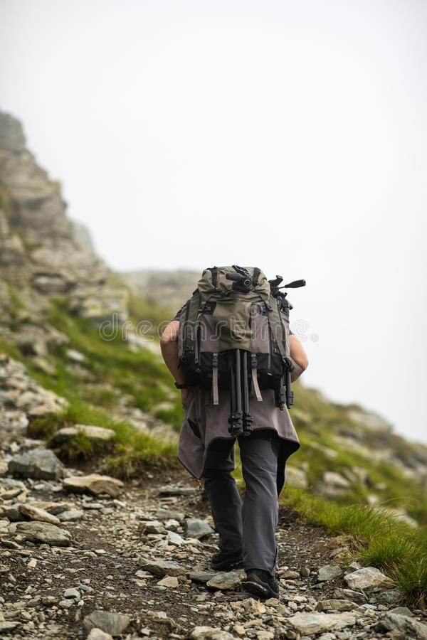Photographer with backpack and camera hiking on a mountain. Trail royalty free stock image