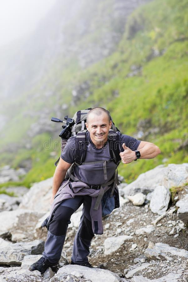 Photographer with backpack and camera hiking on a mountain. Trail royalty free stock images