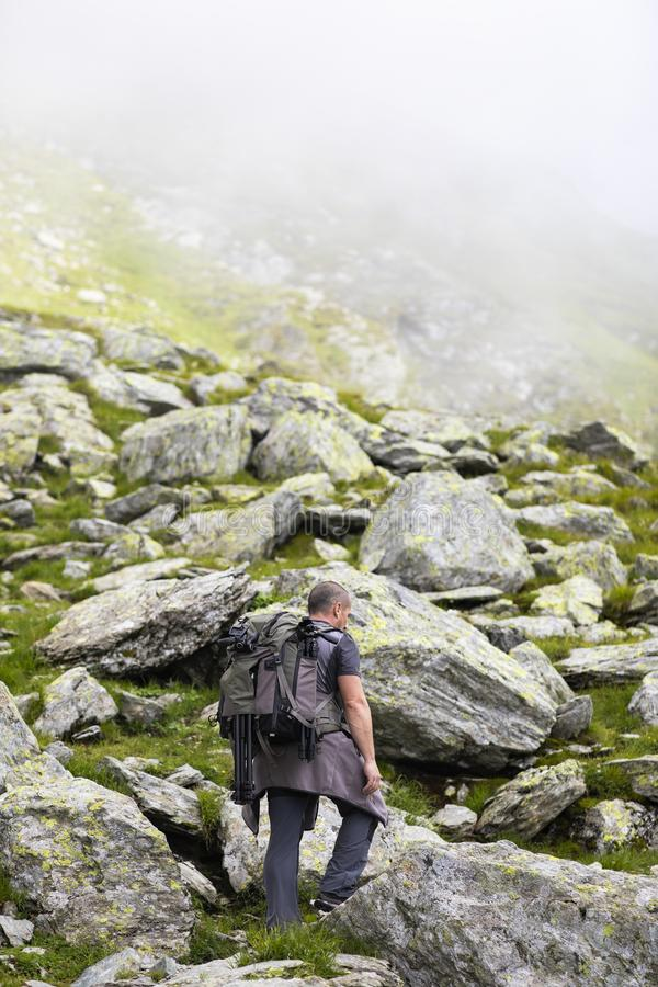 Photographer with backpack and camera hiking on a mountain. Trail stock photos