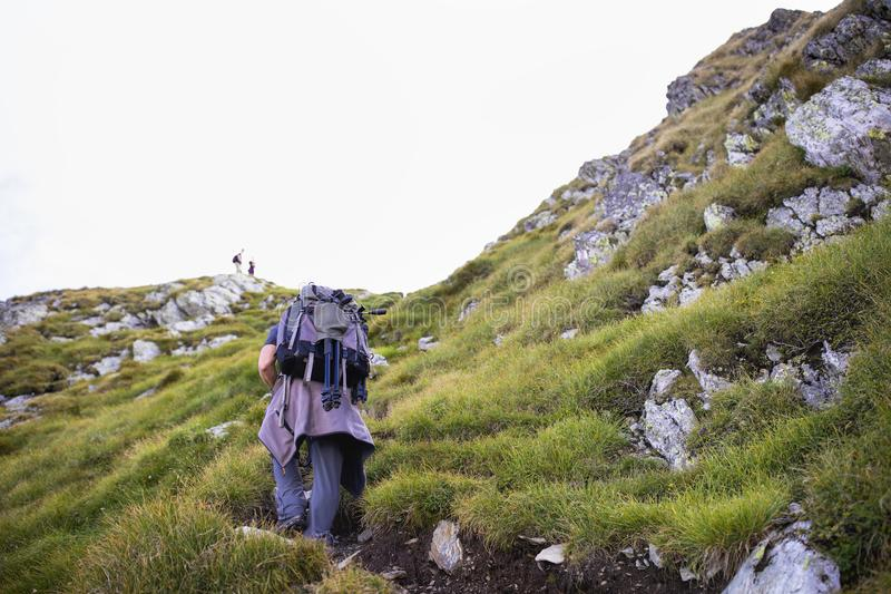 Photographer with backpack and camera hiking on a mountain. Trail stock photo