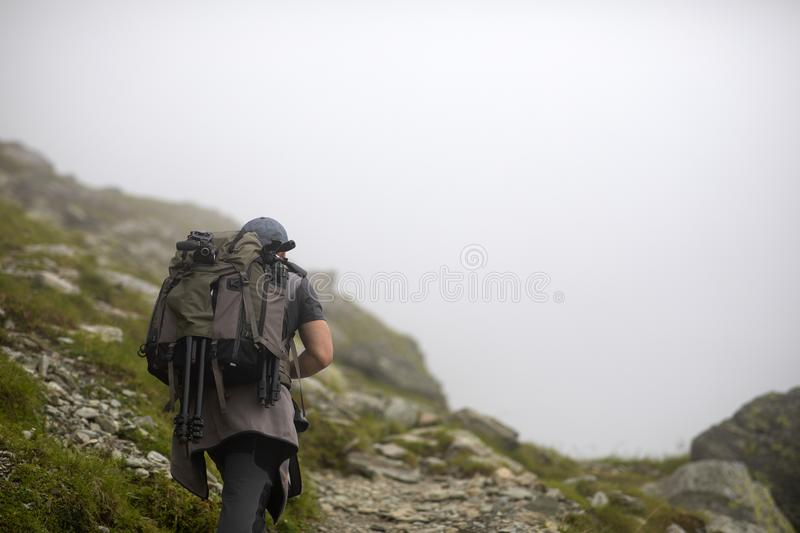 Photographer with backpack and camera hiking on a mountain. Trail stock images