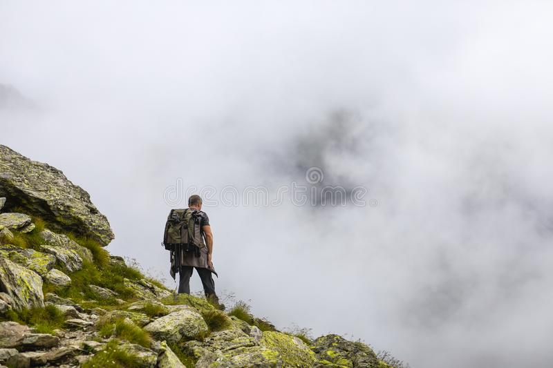Photographer with backpack and camera hiking on a mountain. Trail royalty free stock photography