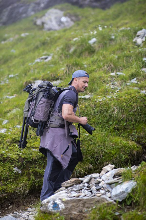 Photographer with backpack and camera hiking on a mountain. Trail stock photography