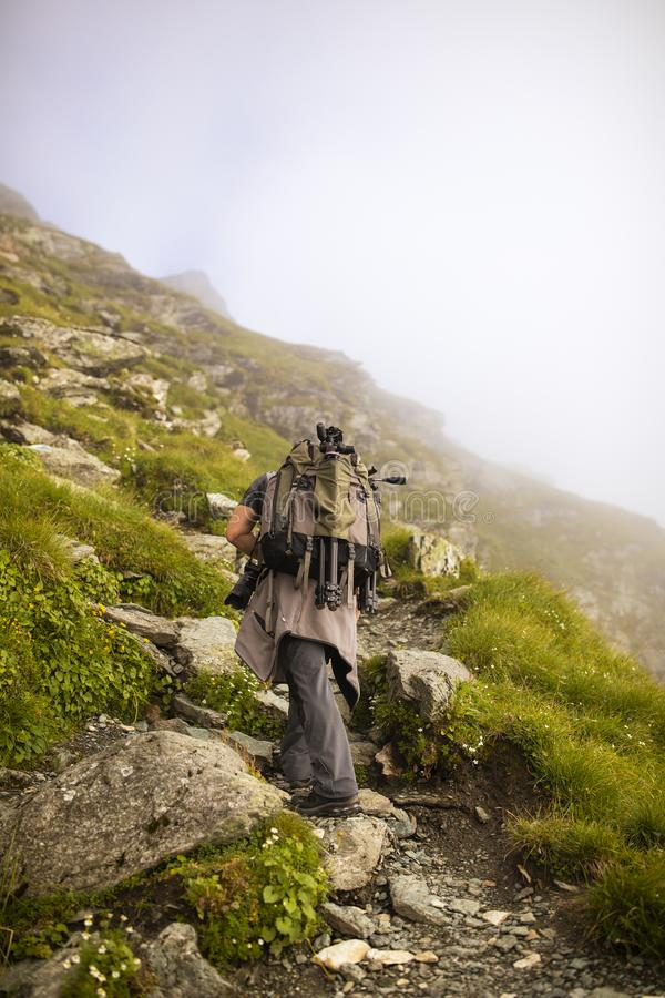 Photographer with backpack and camera hiking on a mountain. Trail royalty free stock photos