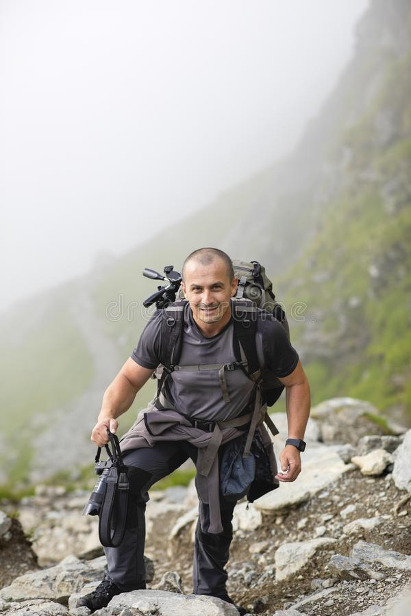 Photographer with backpack and camera hiking on a mountain. Trail royalty free stock photo