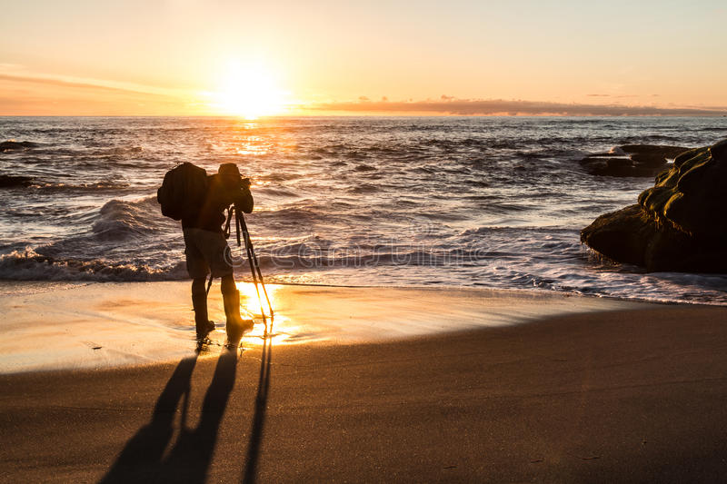 Photographer at Beach Taking Pictures in Silhouette royalty free stock photography