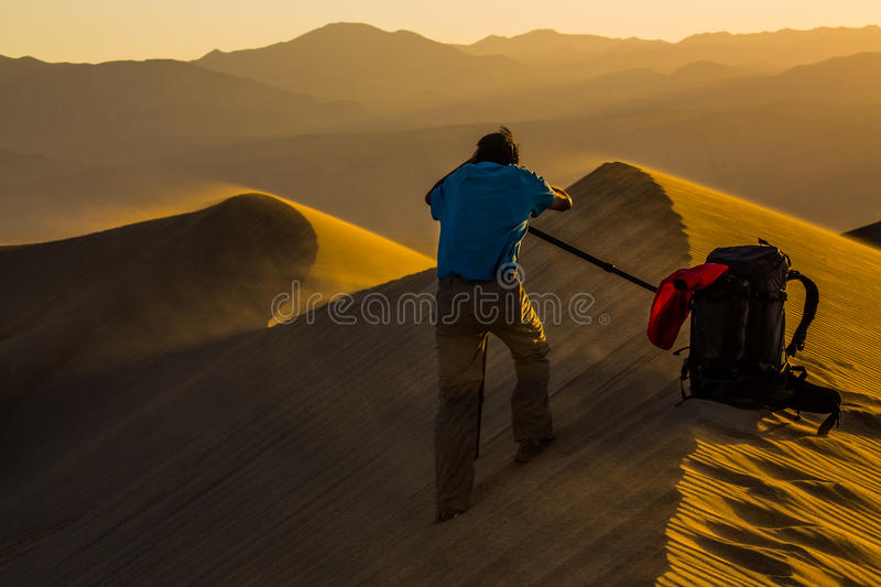 Photographer being blown by wind is framing their shot in Death Valley National Park stock photo