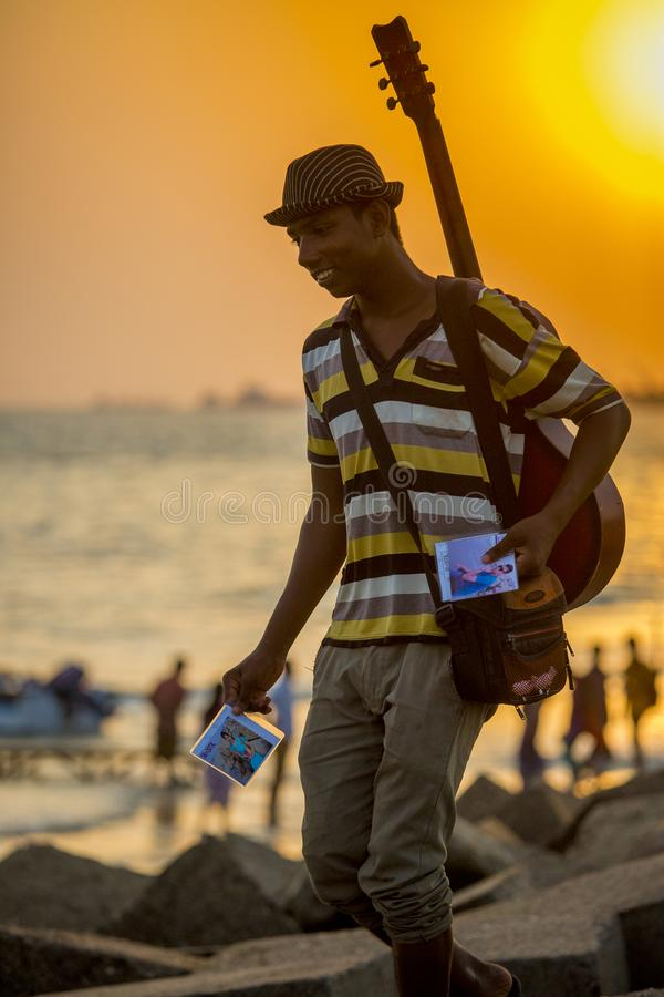 A photographer boy delivered her clients photographs on Patenga beach, Chittagong, Bangladesh. Patenga is a sea beach located 14 kilometres south of the port stock photography