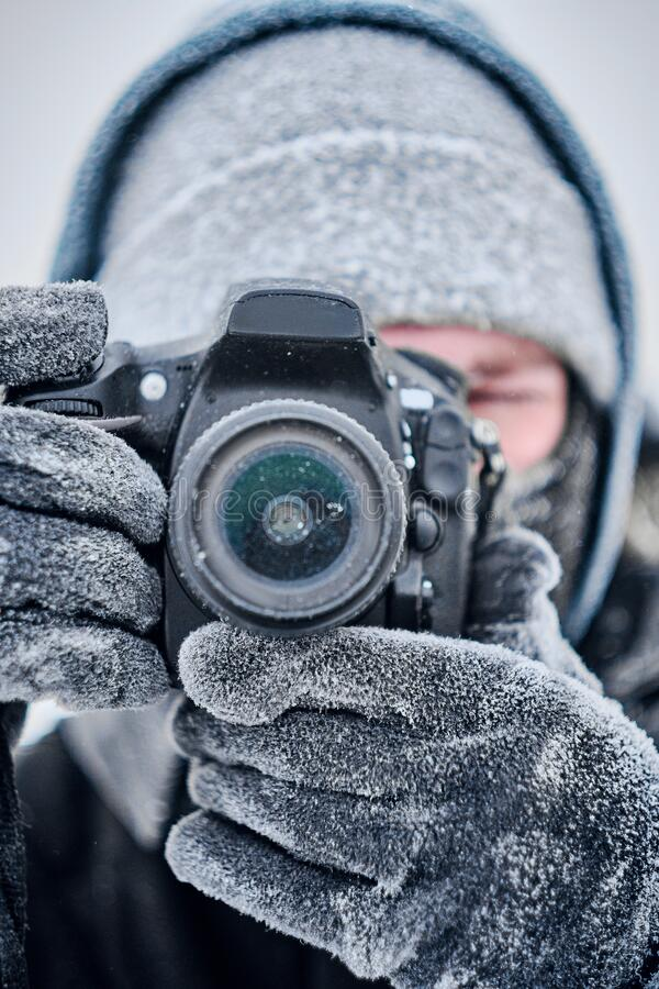 Photographer with camera covered with frost. Portrait of nature photographer with frozen camera wearing balaclava mask on his face, standing in snowy winter stock images