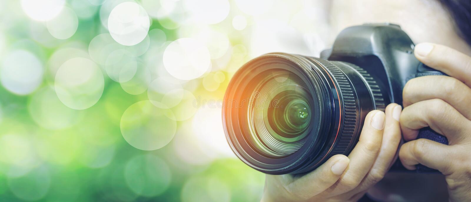 Photographer with camera in hand looking through the camera lens. Bokeo Natural Green Background stock photo
