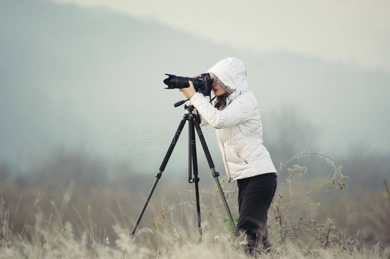 Photographer with camera and tripod outdoor taking landscape picture. Photographer with camera and tripod outdoor making landscape picture, photography, nature royalty free stock image
