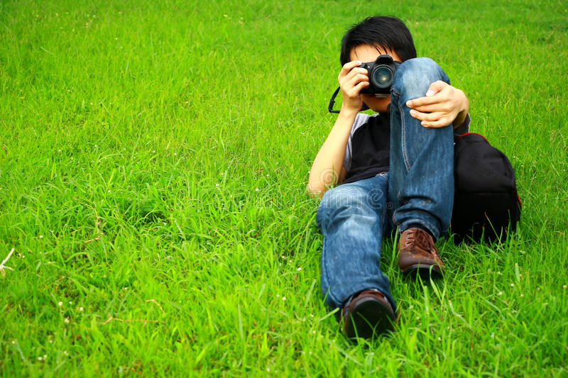 Photographer. Or cameraman prostrate on green grass, self-portrait by two camera royalty free stock photos