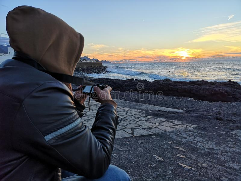 Photographer capturing a sunset. In Agaete, noth coast of gran canaria royalty free stock photography