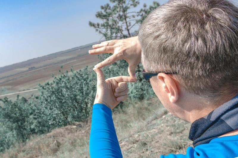 The photographer chooses a location for shooting a beautiful landscape. Hands shaped in viewfinder or frame royalty free stock photos