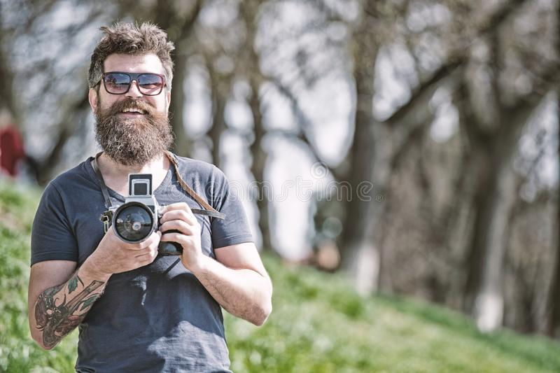 Photographer concept. Man bearded hipster photographer hold vintage camera. Photographer with beard and mustache amateur. Photographer nature background. Man stock photos