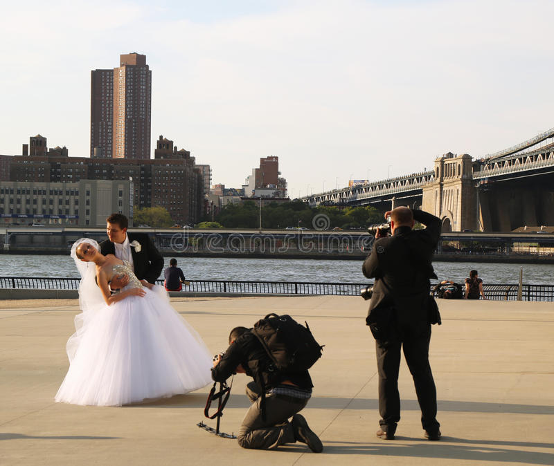 Photographer with the crew shooting newlywed couple under Brooklyn Bridge stock images