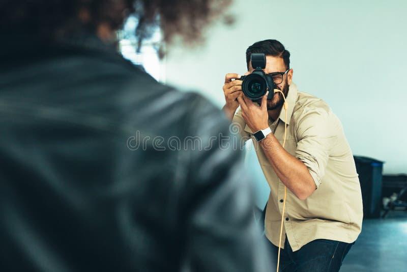 Photographer doing a photo shoot in a studio. Photographer shooting photographs of a model in a studio. Rear view of a model posing for photograph during a photo stock photos