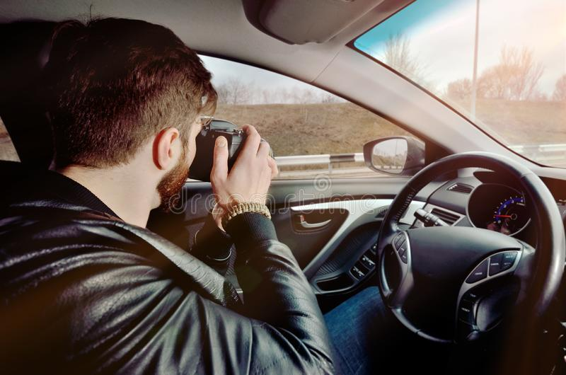 The photographer is driving a car. Beautiful guy with a photo camera. Examines photos in the car. The traveler photographs through royalty free stock photos