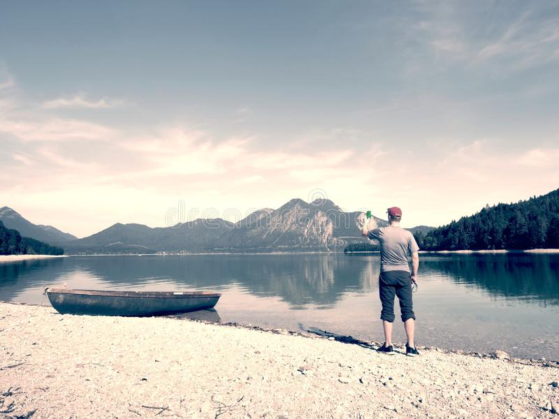 Photographer with eye at viewfinder is taking photo of lake with Alps stock photography