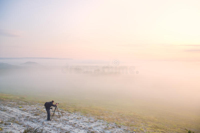 The photographer at foggy meadow royalty free stock images