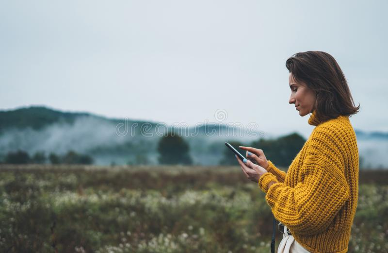 Photographer girl hold in hands mobile phone typing message on smartphone on background autumn froggy mountain, internet online. Concept stock photo