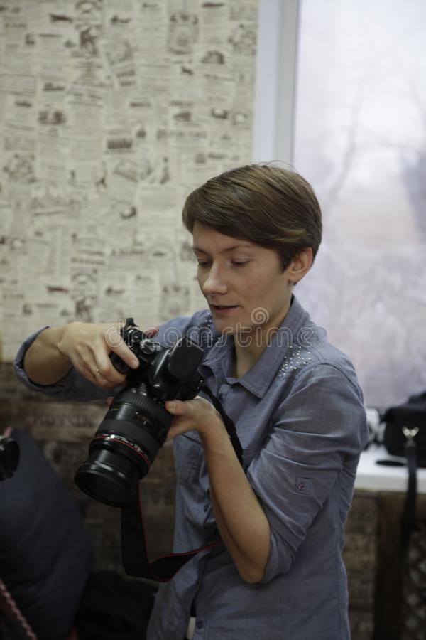 Photographer girl looks photos camera smiling. Photographer girl looks at photos in the camera and smiling royalty free stock photo
