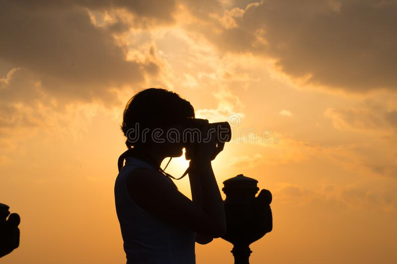 Photographer girl, photographing the sunset 2. Girl photographer, photographing the sunset, her silhouette hides the sun behind her royalty free stock photos