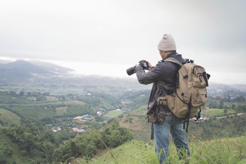 Photographer hand holding camera and standing on top of the mountain in nature. Travel concept. Vintage tone royalty free stock photography