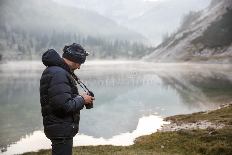 Photographer holding a camera, checking photos royalty free stock images