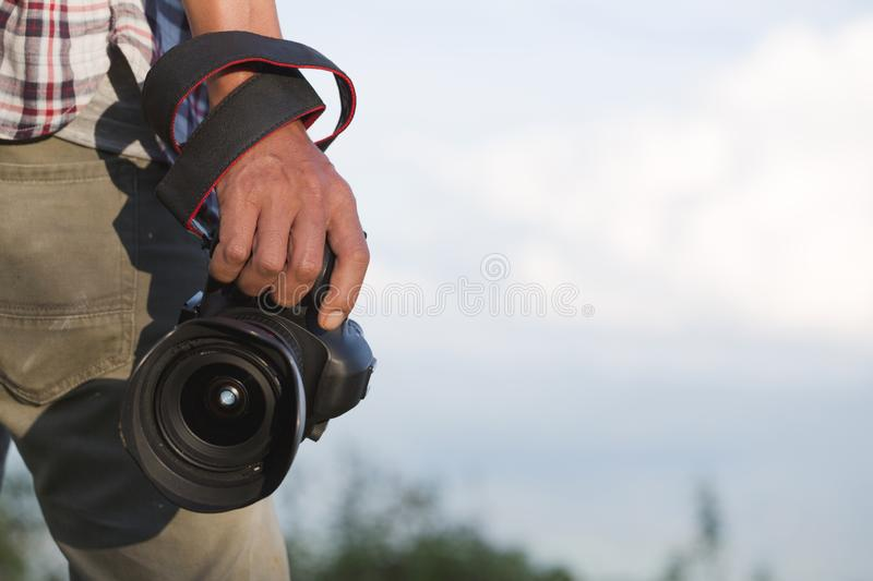 Photographer holding his camera. Travelers hold a DSLR camera on stock image